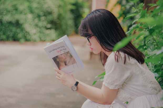 close up photography of woman reading book